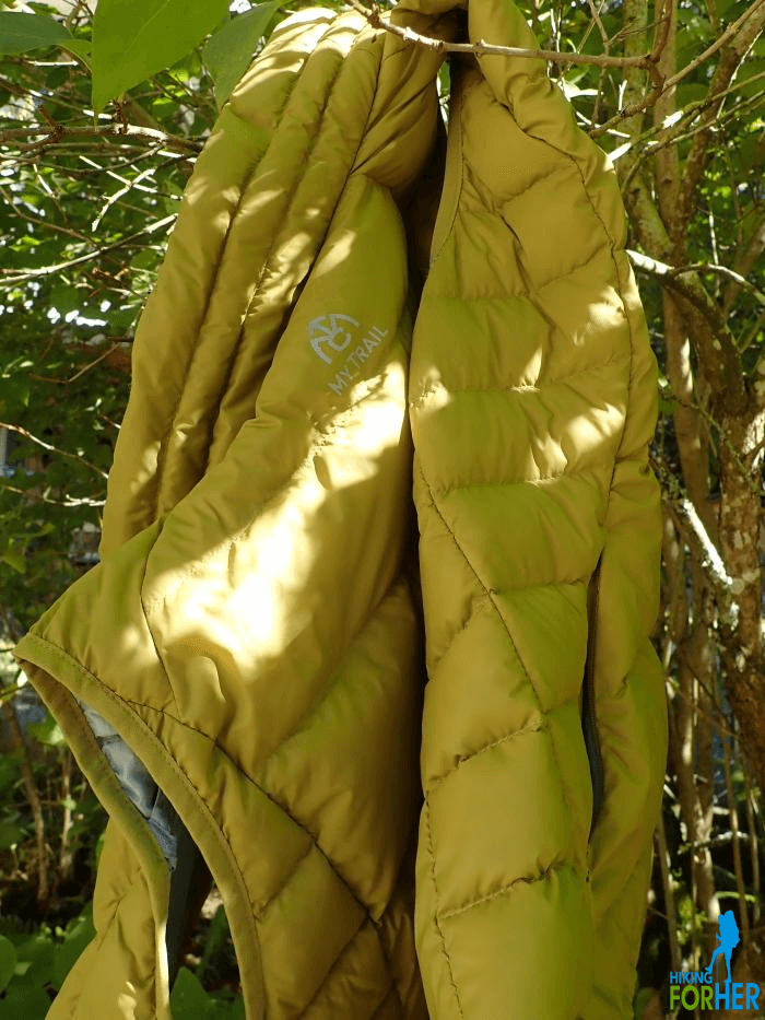 Yellowish green down hiking vest hanging from branches in dappled sunlight