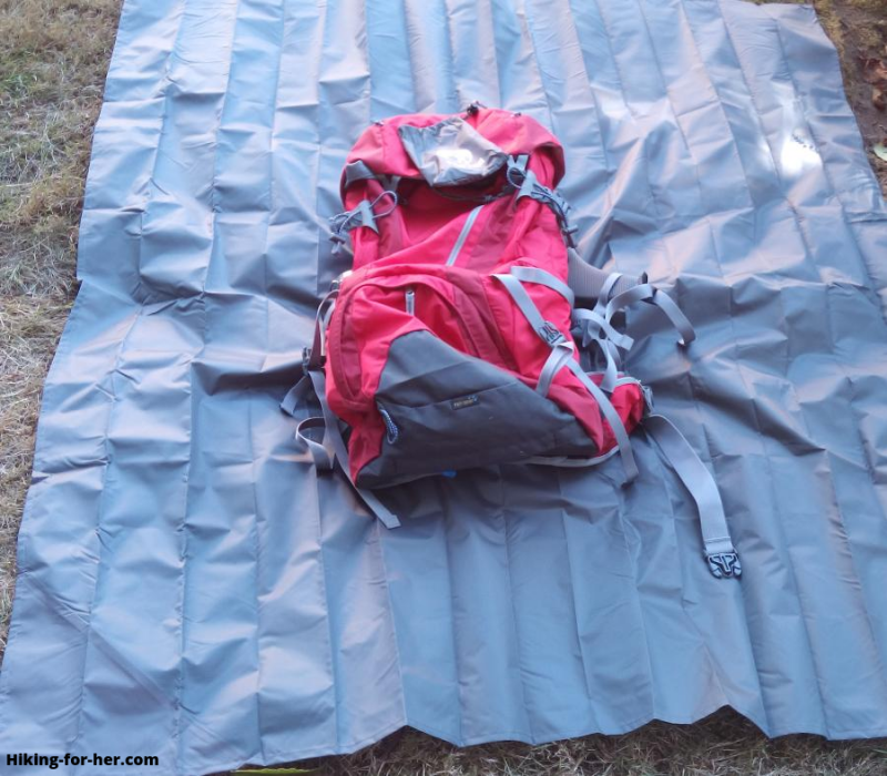 Red hiking backpack lying on blue tarp