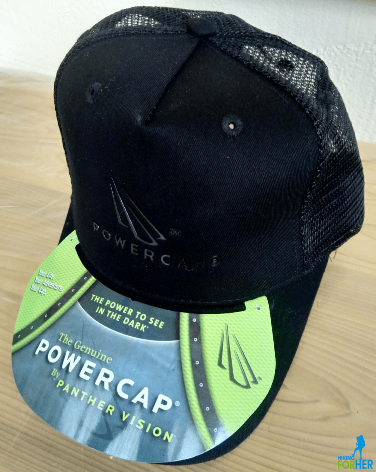 Black ball cap style Powercap with green and gray tag on bill