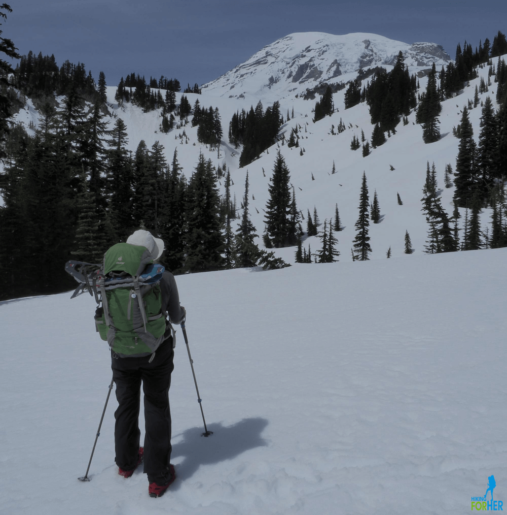 Female hiker wearing traction devices on boots, gazing at Mount Rainier