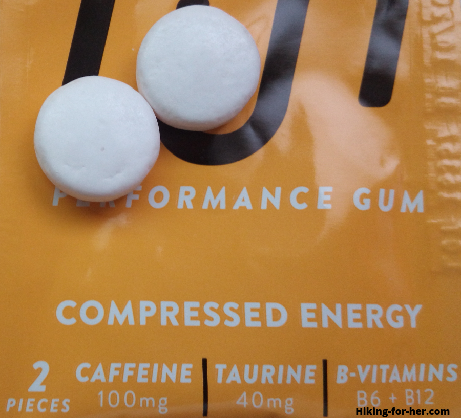 Closeup of round pellets of performance gum sitting on top of a yellow package
