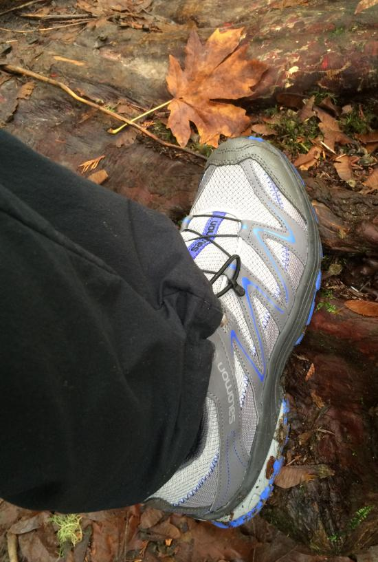 Hiking shoe on trail with autumn leaves