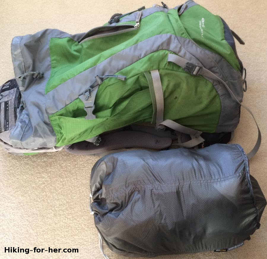 Green hiking backpack lying next to a GobiGear segmented stuff sack for size comparison