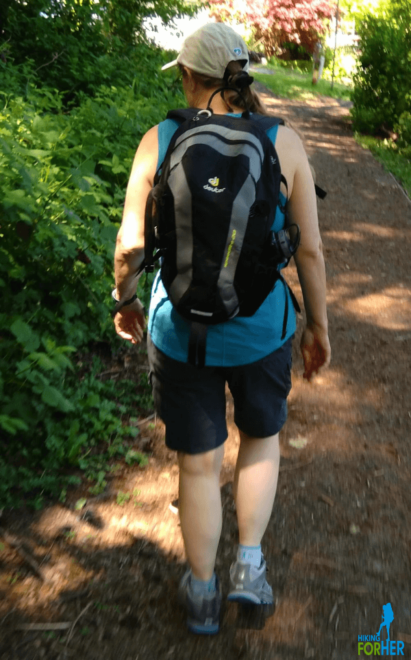 Female hiker on the trail with backpack, dressed for warm weather hiking