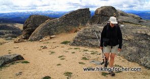 female hiker with trekking poles and backpack on a trail surrounded by large boulders