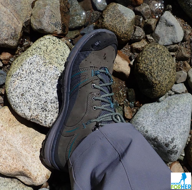 Closeup of hiking boot and gray rocks along a river bank