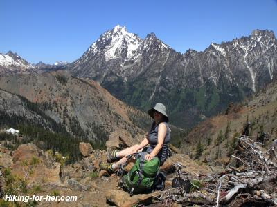 Tall peaks behind hiker sitting on rocks holding her green backpack