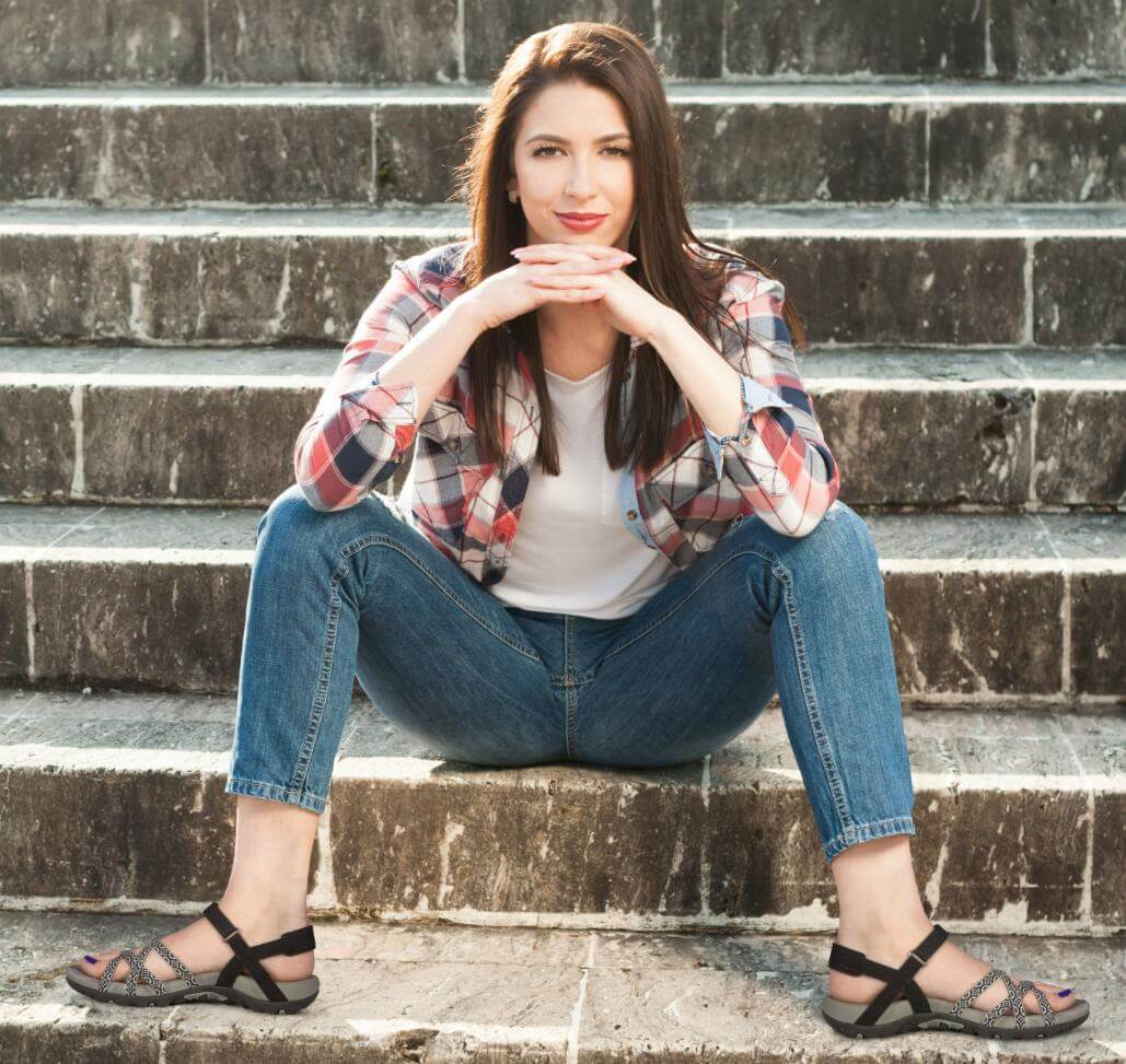 Female in jeans and plaid shirt showing off a pair of sandals on her feet