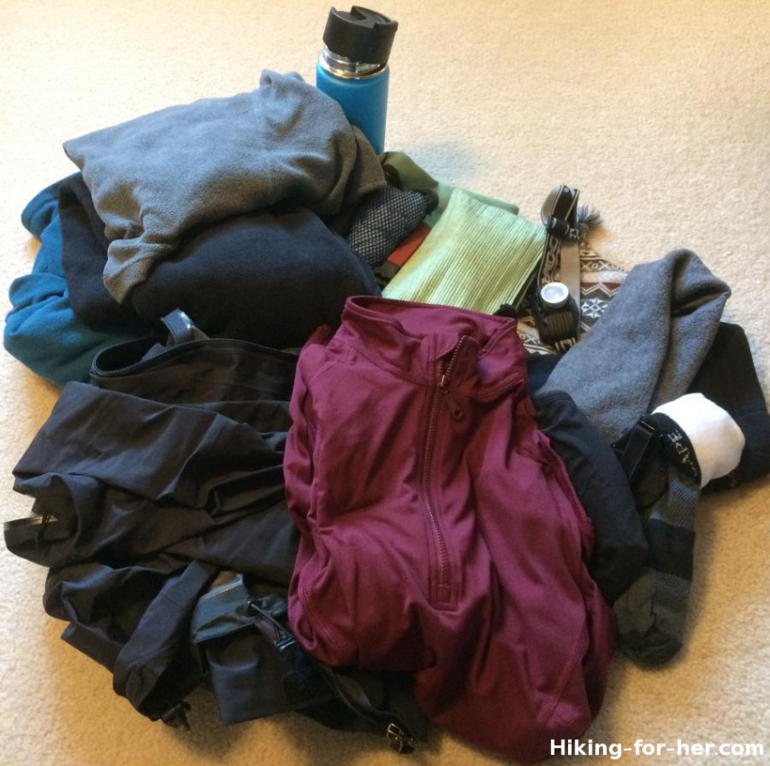A stack of backpacking clothing and water bottle, ready to go into a backpack for a hiking trip