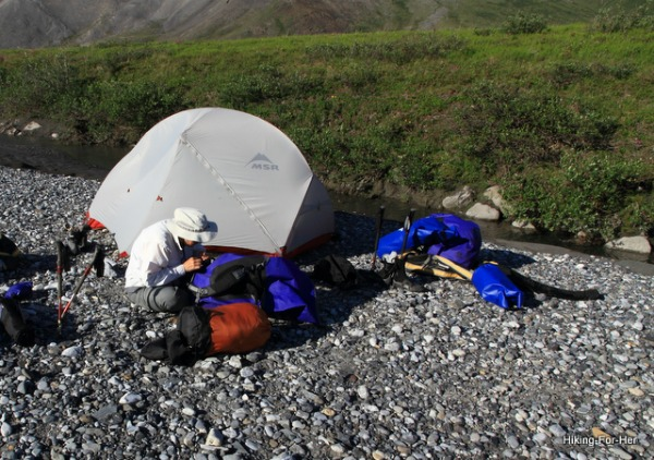 Female hiker doing a field repair to hiking gear on a river gravel bar with her white backpacking tent behind her