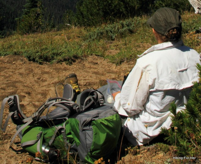 Female hiker in a white shirt, sitting in the dirt with a green backpack beside her
