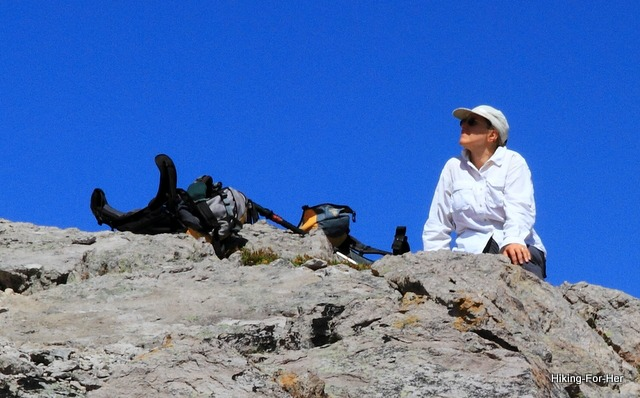 True blue sky and female hiker in a white shirt sitting on a mountain ridge