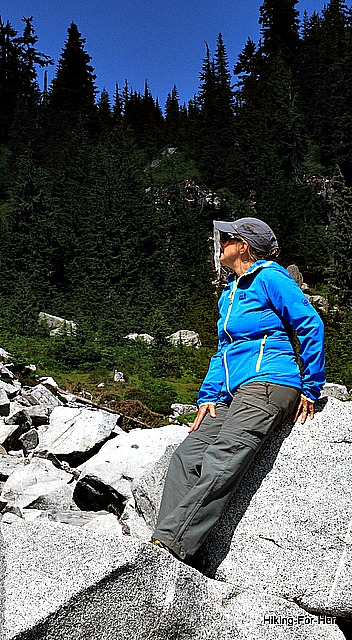 Female hiker leaning against gray slabs of rock in the mountains