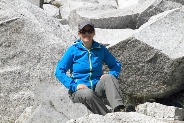 Female hiker in bright blue jacket and hat seated on gray slabs of rock