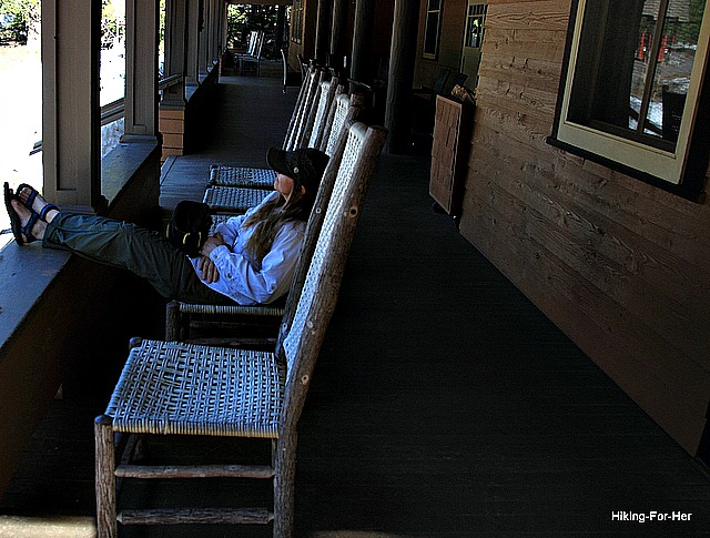 Woman sitting on the porch of Longmire Inn, Mt. Rainier National Park, with her feet up after a long day of hiking