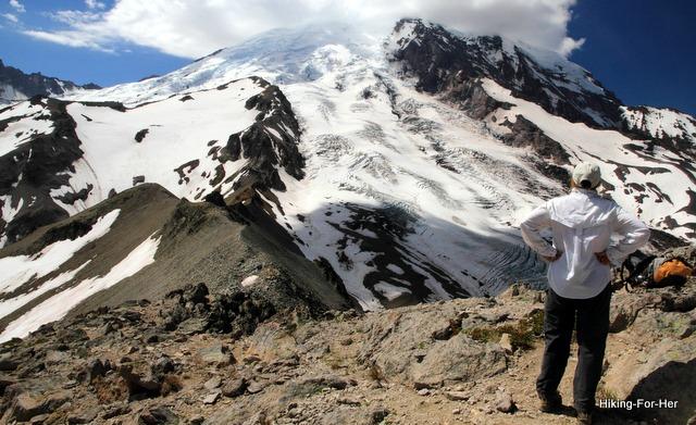 Woman hiker gazing at Mt. Rainier from a hiking trail