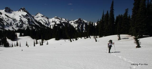 Female snowshoer crossing a flat valley using trekking poles