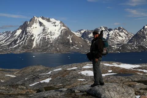 Female hiker looking at East Greenland snowy mountains and fjord