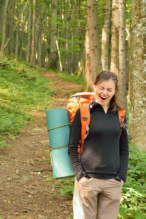Yawning female hiker with sleeping pad