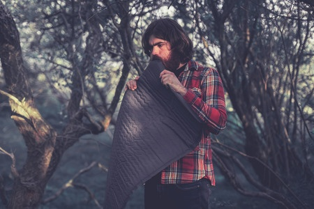 Male hiker in plaid shirt blowing up an air mattress