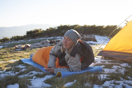 female hiker reclining in sleeping bag outside of backpacking tent