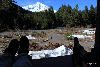 Two pairs of feet propped up on a porch rail after a long hike, with Mount Rainier in the background