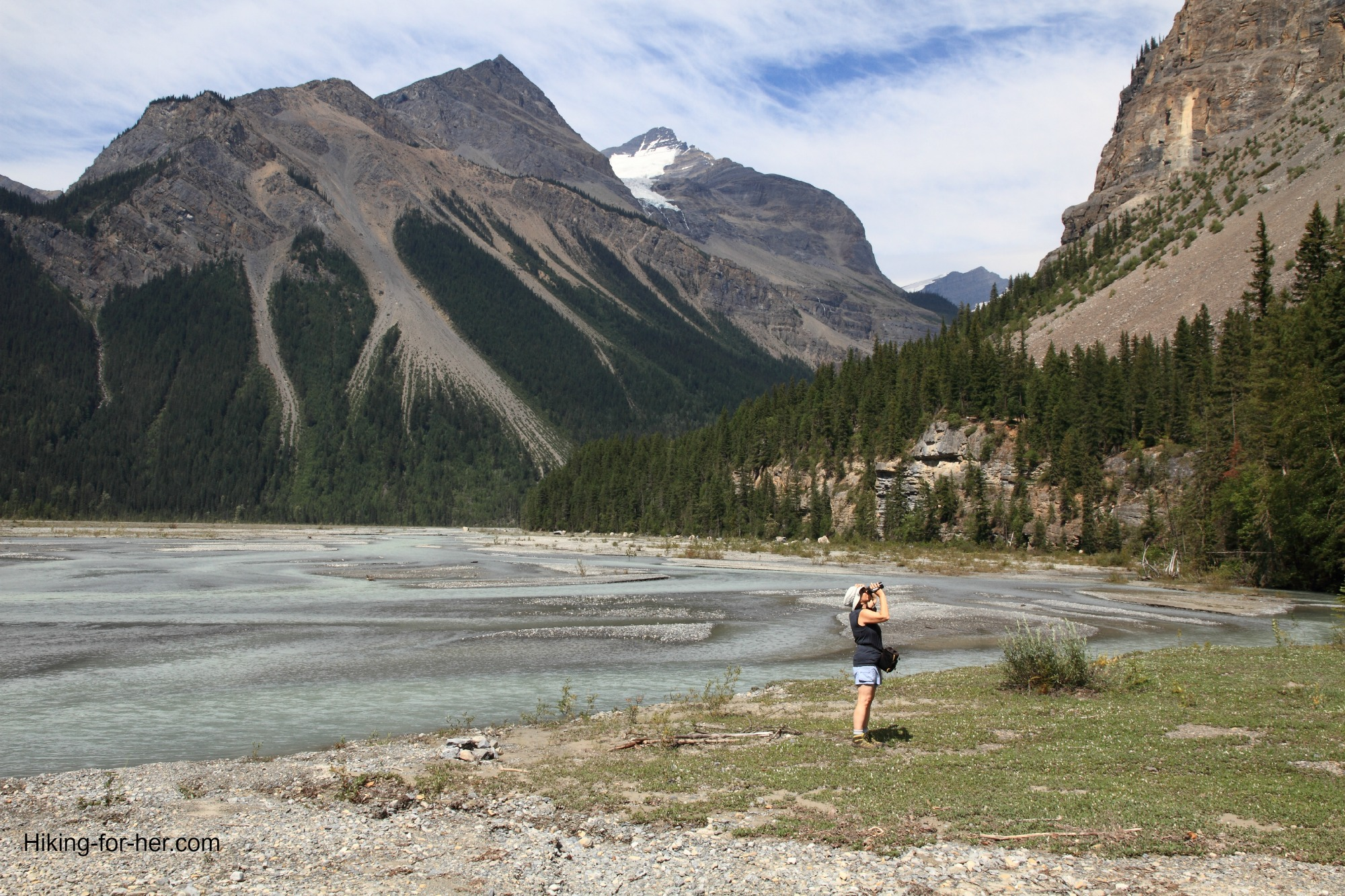 Female hiker taking photos at a lake surrounded by steep rugged mountains