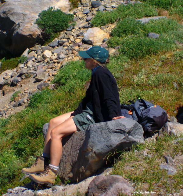 Female hiker wearing green shorts, black hiking jacket and rugged leather boots sitting on a boulder in the mountains