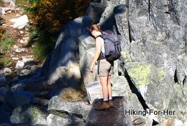 Female hiker wearing backpack and standing on a log bridge over a creek surrounded by boulders