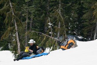 Female hiker sitting on a blue tarp on a snowy mountainside
