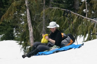Female hiker sitting on blue tarp on top of snow, eating lunch