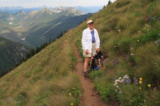 Female hiker on mountain trail surrounded by alpine wildflowers