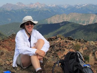 Female hiker practicing sun burn avoidance with a hat and long sleeves