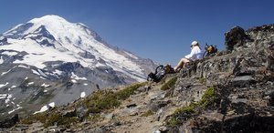 Woman hiker in a long sleeve white shirt and hiking hat gazing at Mt. Rainier with her backpack beside her