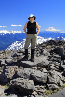 Female hiker wearing a sun hat, sleeveless black shirt and hiking pants, standing with her hands in her pockets atop a boulder field on a mountain slop