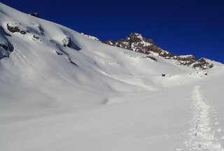 snowshoe tracks on pristine snowfield below a rocky outcrop with bright blue sky