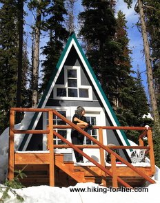Woman standing on porch of snowy A frame cabin