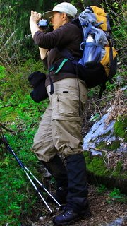Female hiker with pack, gaiters and camera