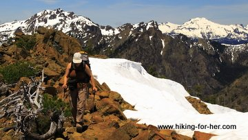 Female hiker on rocks and snow in high alpine terrain
