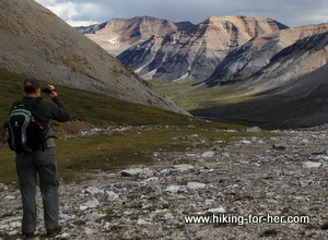 Female hiker with backpack taking photo of unnamed mountain in the backcountry of the Yukon