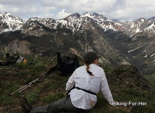 Female hiker enjoying a view of snow covered mountains