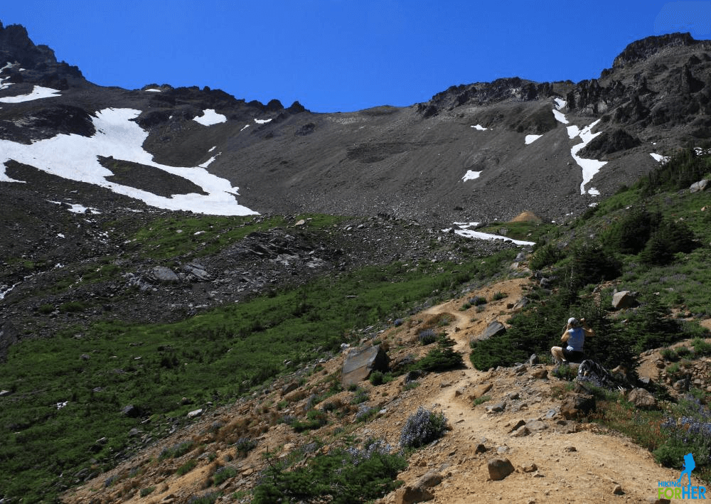 Winding, rocky hiking trail in alpine terrain with snow fields in the distance