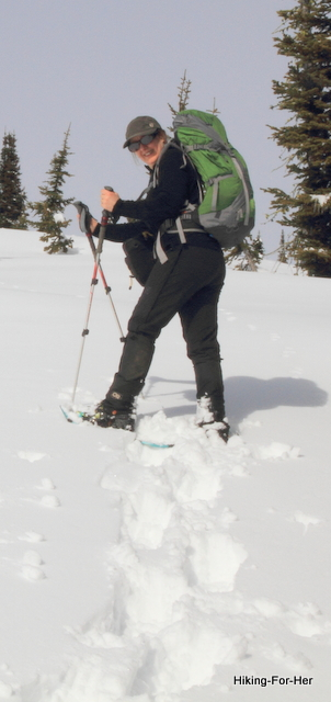 Female snowshoer with green backpack wearing sunglasses