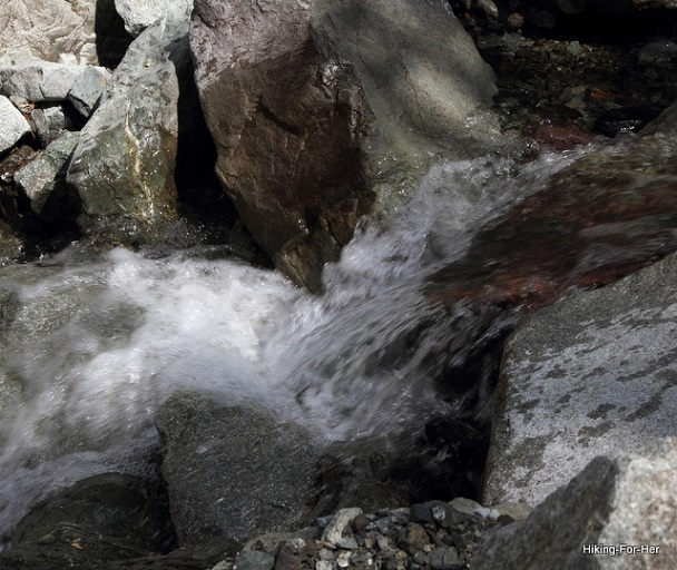 Clear rushing water over boulders in a mountain stream