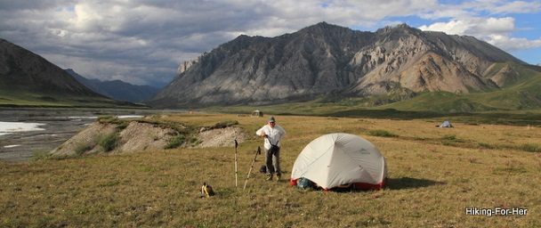 Woman setting up backpacking tent surrounded by mountains