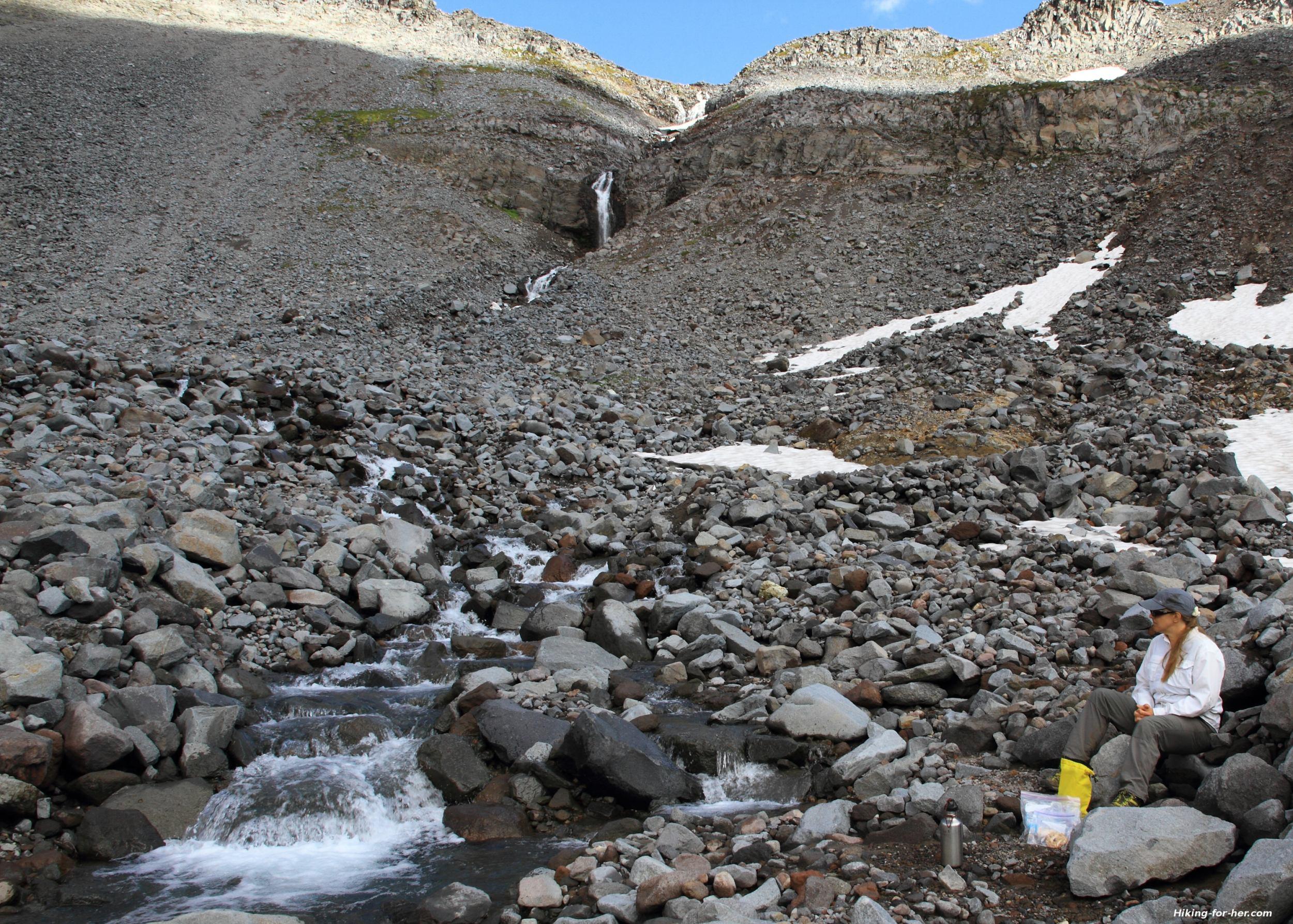 Hiker resting near a boulder filled stream