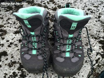 A pair of unlaced gray and turquoise hiking boots, on a granite rock