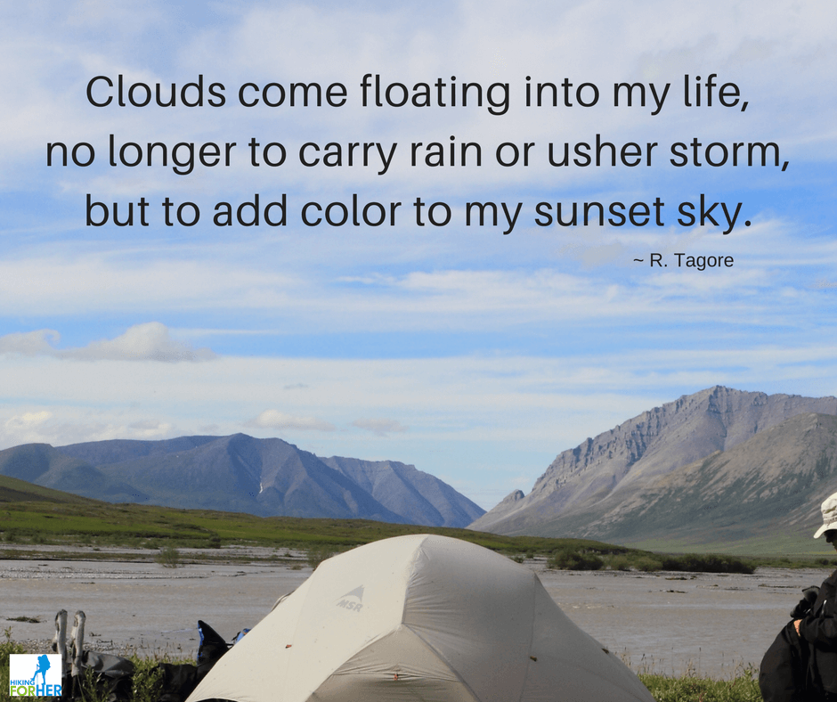 Backpacker and dome tent with wide river and mountains in background