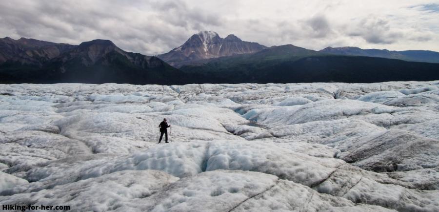 Hiker striding across surface of Nizina Glacier, Alaska