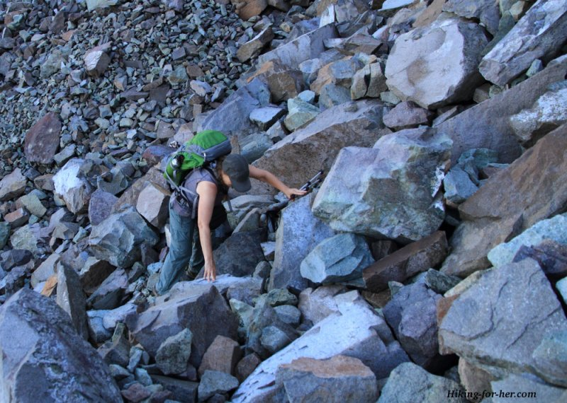 Hiker wearing a green backpack, working her way up a boulder field using her hands and knees
